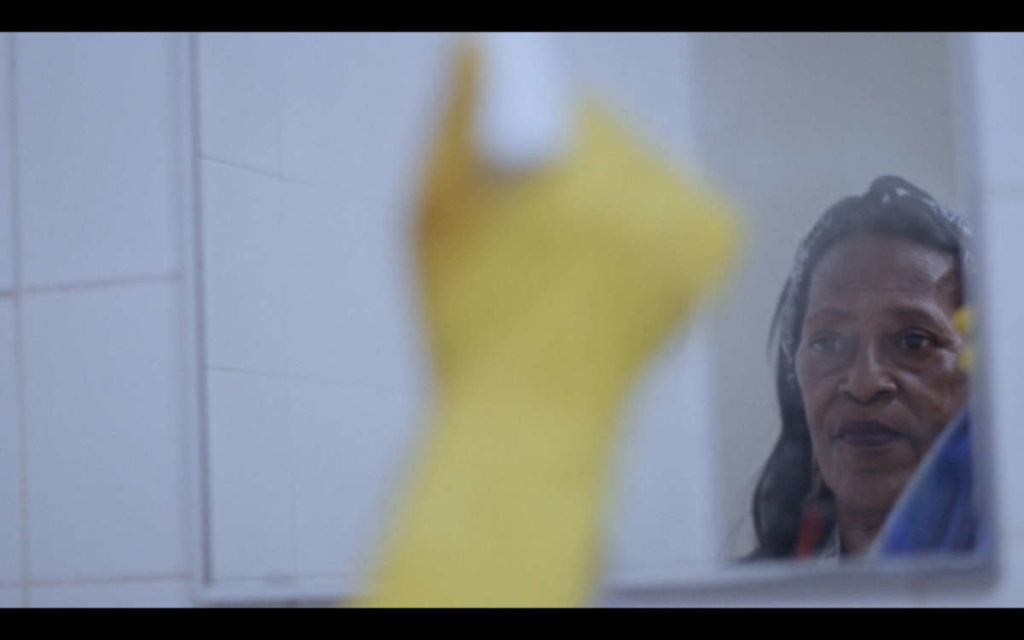 Woman with yellow gloves cleaning a mirror