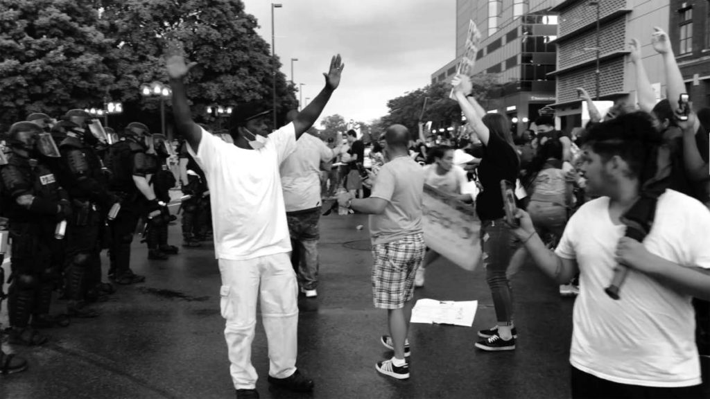 Black and white image of people protesting in the streets